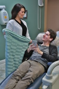 Dentist Giving Blanket To Patient In Dental Chair